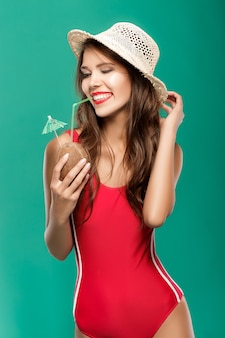 Portrait of beautiful seductive sexy woman drinks summer cocktail in coconut on green background
