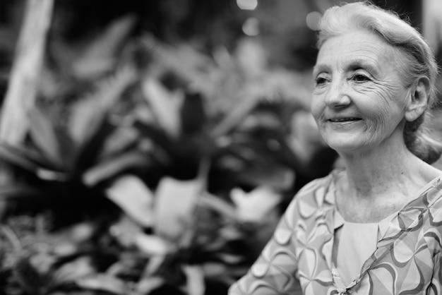 Portrait of beautiful senior tourist woman relaxing around the city of bangkok in black and white Premium Photo