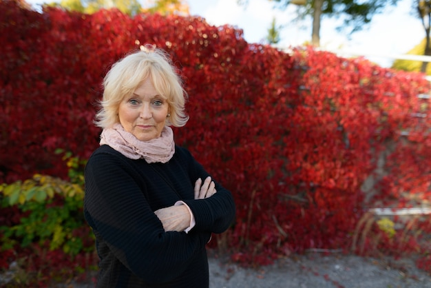 Portrait of beautiful senior woman with short blond hair relaxing at the park outdoors in autumn