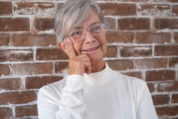 Portrait of beautiful senior woman with white hair - brick wall in background