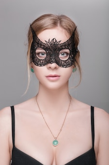 Portrait of beautiful sensual blond woman with green eyes in black lace mask on a dark background. venetian mask