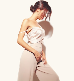 Portrait of beautiful sensual brunette woman girl in elegant white classic clothes and wide pants on white background