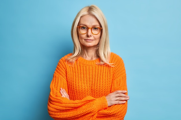 Portrait of beautiful serious middle aged woman keeps hands crossed wears spectacles and orange sweater looks confidently listens attentively interlocutor.