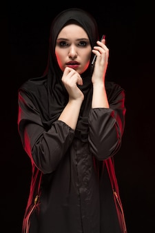 Portrait of beautiful serious scared frightened young muslim woman wearing black hijab calling for help on black