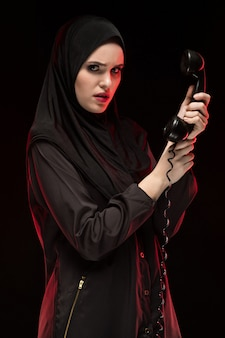 Portrait of beautiful serious scared young muslim woman wearing black hijab calling for help