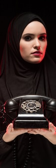 Portrait of beautiful serious scared young muslim woman wearing black hijab offering telephone to call as choice concept on black