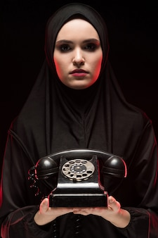 Portrait of beautiful serious scared young muslim woman wearing black hijab offering telephone to call as choice concept