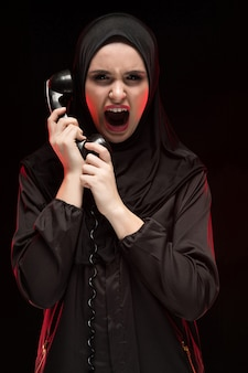 Portrait of beautiful serious scared young muslim woman wearing black hijab screaming calling for help on black
