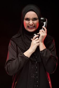 Portrait of beautiful serious scared young muslim woman wearing black hijab screaming calling for help  black