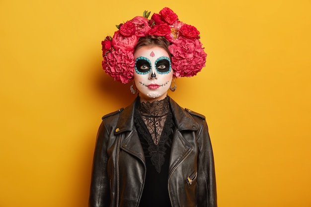 Portrait of beautiful serious woman has creative vivid makeup, wears flower wreath, black clothes, tries be scarying, comes on halloween holiday party or day of dead
