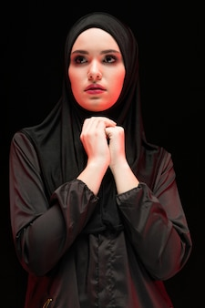 Portrait of beautiful serious young muslim woman wearing black hijab with hands near her face as pray concept