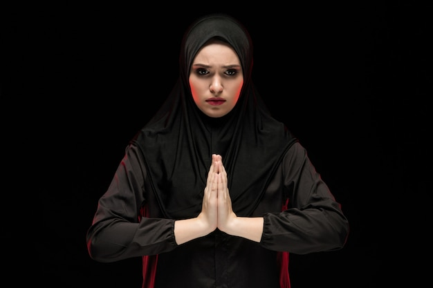 Portrait of beautiful serious young muslim woman wearing black hijab with hands near her face as praying concept on black background