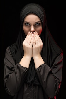 Portrait of beautiful serious young muslim woman wearing black hijab with hands near her face as praying concept