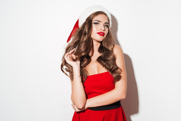 Portrait of a beautiful sexy brunette woman in red christmas dress standing isolated over white surface