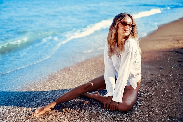 Portrait of beautiful sexy caucasian sunbathed woman in sunglasses with long hair in swimsuit lying on summer beach