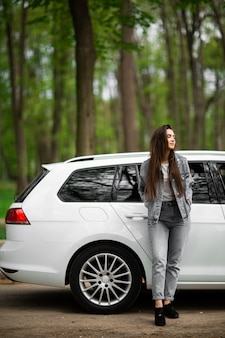 Portrait of beautiful sexy fashion brunette woman model in jeans jacket standing near luxury white car and relaxes. fashion concept. idea for girl photoshoot with car. vertical.