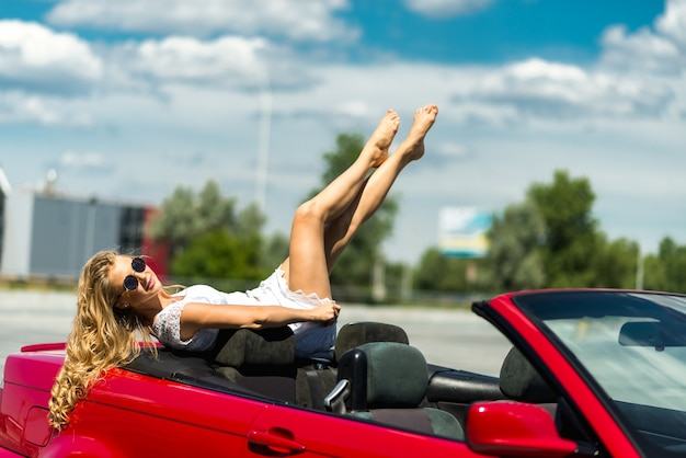 Portrait of beautiful sexy fashion woman model in sunglasses sitting in luxury red convertible car with sea and sky background. young woman driving on road trip on sunny summer day. sea and sky. red cabrio.