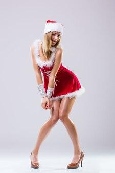 Ritratto di bella donna sexy andare andare ballerino che indossa come babbo natale isolato su sfondo bianco