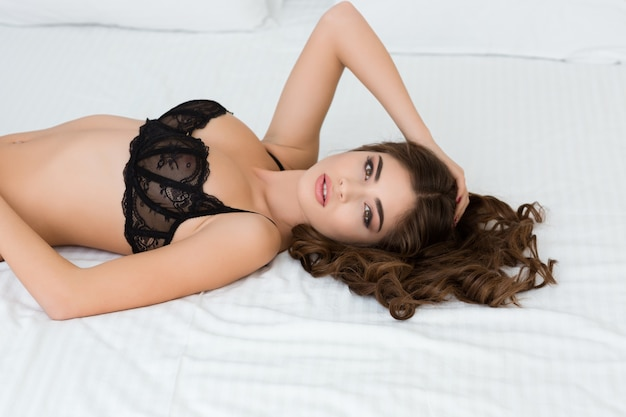 Portrait of a beautiful sexy woman in lingerie lying on the bed and looking at camera