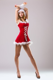 Portrait of beautiful sexy woman wearing like santa claus dancing isolated on white background