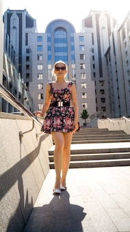Portrait of beautiful sexy young woman in short dress and sunglasses posing on stone staircase in sun rays