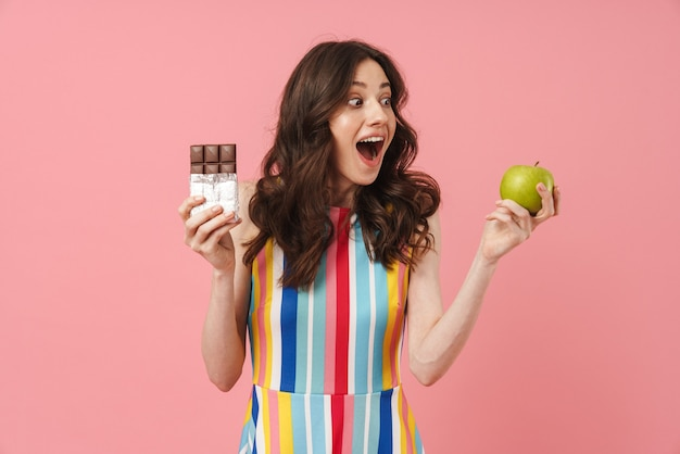 Portrait of beautiful shocked cute woman posing isolated over pink wall holding apple and chocolate
