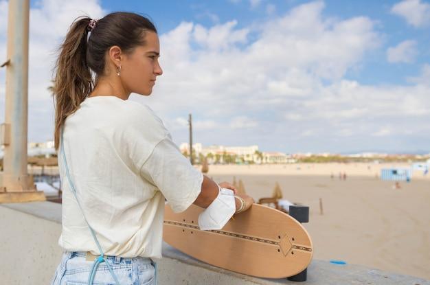 思慮深く無限に向かって見ている肖像画の美しいスケーターの女の子