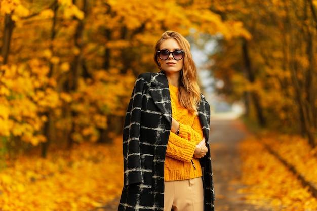 빈티지 니트 스웨터와 코트를 입은 세련된 안경을 쓴 아름다운 슬라브 소녀 초상화가 밝은 노란색 단풍으로 화려한 가을 공원을 걷고 있다