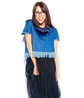 Ritratto di bello modello sorridente astuto della donna del brunette dei pantaloni a vita bassa in vestiti e vetri alla moda casuali delle blue jeans isolati su bianco che mostra la sua lingua