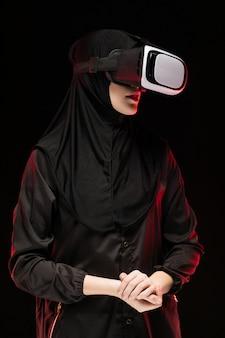 Portrait of beautiful smart young muslim woman wearing black hijab using virtual reality headset