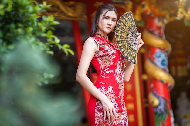 Портрет красивой улыбающейся молодой азиатской женщины в красном традиционном китайском чонсаме, держащей китайский фаннинг на фестивале китайского нового года в китайском храме