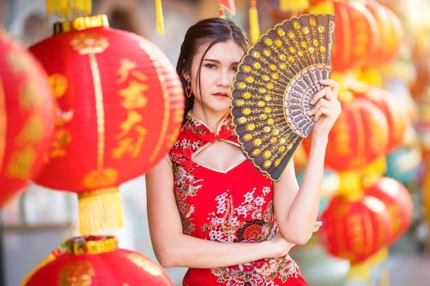 Портрет красивой улыбающейся молодой азиатской женщины в красном традиционном китайском чонсаме, держащей с бумажными фонариками китайский фаннинг на китайском новогоднем фестивале в китайском храме