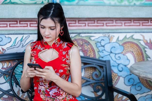 Портрет красивой улыбающейся азиатской молодой женщины в красном традиционном китайском чонсаме и написания сообщения на смартфоне для фестиваля китайского нового года в китайском храме