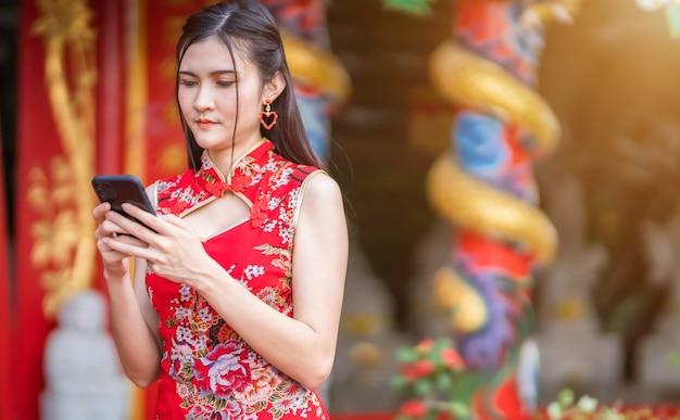 Портрет красивой улыбки азиатской молодой женщины в красном традиционном китайском чонсаме и написании сообщения на смартфоне