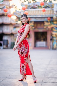 Portrait beautiful smiles asian young woman wearing red traditional chinese cheongsam, for chinese new year festival at chinese shrine