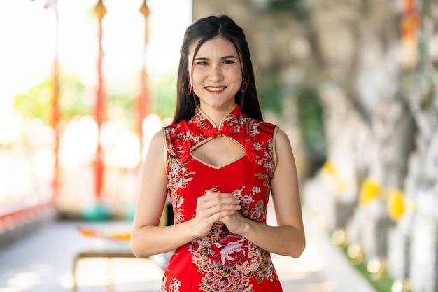 Портрет красивой улыбающейся азиатской молодой женщины в красном традиционном китайском чонсаме на фестивале китайского нового года в китайском храме