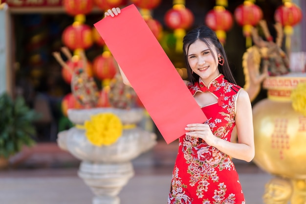 Portrait beautiful smiles asian young woman wearing red traditional chinese cheongsam, holding show blank spring paper red for chinese new year festival at chinese shrine