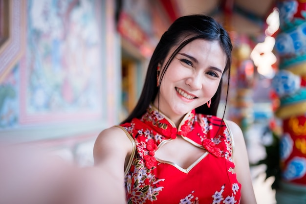 Portrait beautiful smiles asian young woman wearing red traditional chinese cheongsam, taking a selfie with smartphone for chinese new year festival at chinese shrine