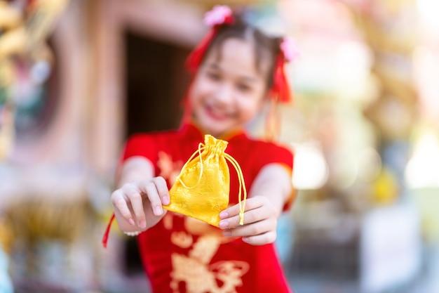 세로 아름다운 미소 빨간색 전통 중국 치파오를 입고 귀여운 아시아 소녀, 초점은 중국 신사에서 구정 축제를위한 황금 돈 가방을 보여