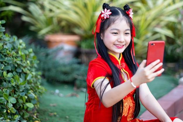 세로 아름다운 미소 귀여운 아시아 소녀 빨간색 전통 중국 치파오를 입고 스마트 폰으로 셀카를 복용