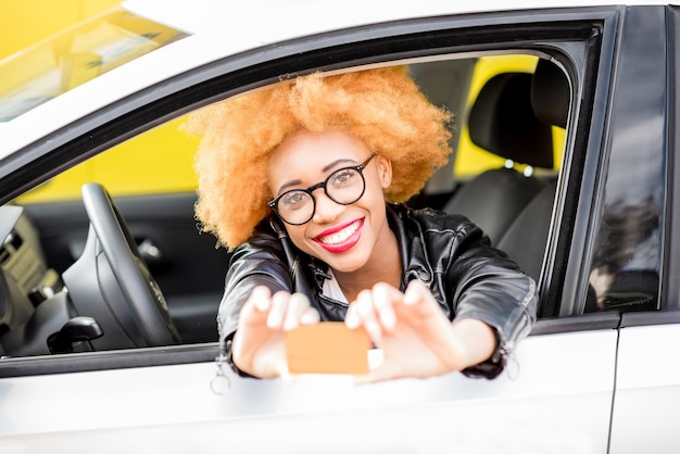 Portrait of a beautiful smiling african woman in leather jacket showing a card with blank space sitting in the car on the yellow background