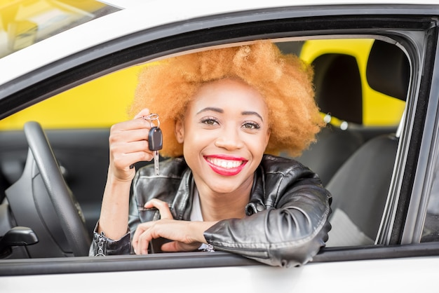 Portrait of a beautiful smiling african woman in leather jacket showing keys in the car on the yellow background