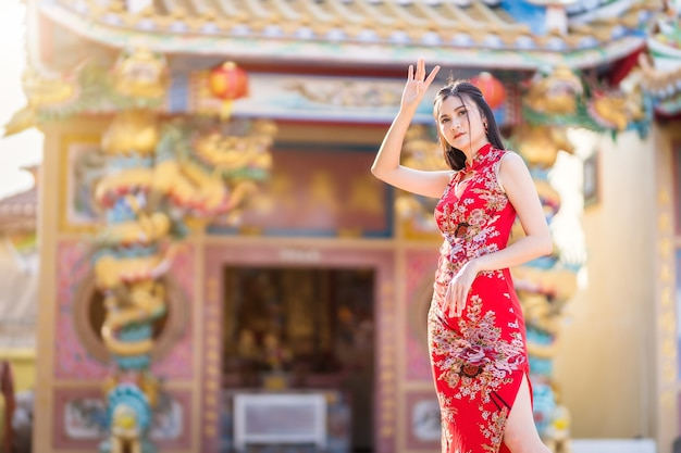 Portrait of beautiful smiling asian young woman wearing red traditional chinese cheongsam, for chinese new year festival at chinese shrine