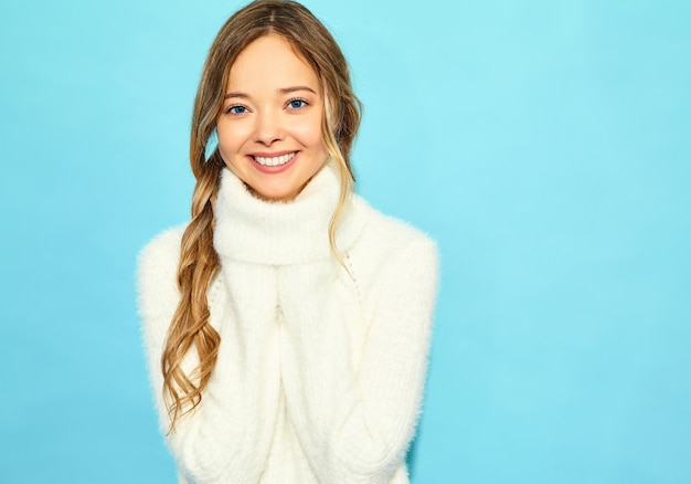 Portrait of beautiful smiling blond gorgeous woman. woman standing in stylish white sweater, on blue wall. concept of winter