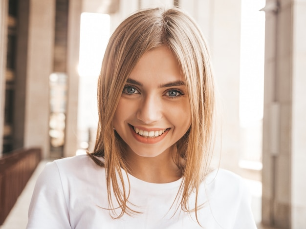 Portrait of beautiful smiling blond model dressed in summer hipster  clothes. trendy girl posing in the street background. funny and positive woman
