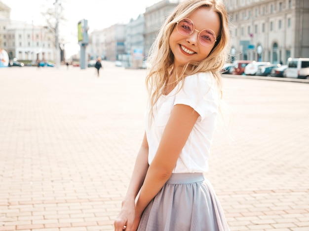 Portrait of beautiful smiling blond model dressed in summer hipster  clothes. trendy girl posing in the street   in round sunglasses. funny and positive woman having fun