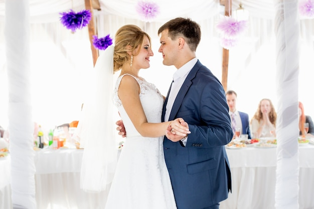 Portrait of beautiful smiling bride and groom dancing in restaurant hall