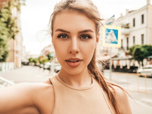 Ritratto di bella ragazza bruna sorridente in abiti estivi