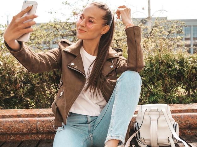 Portrait of beautiful smiling brunette girl in summer hipster jacket and jeans model taking selfie on smartphone