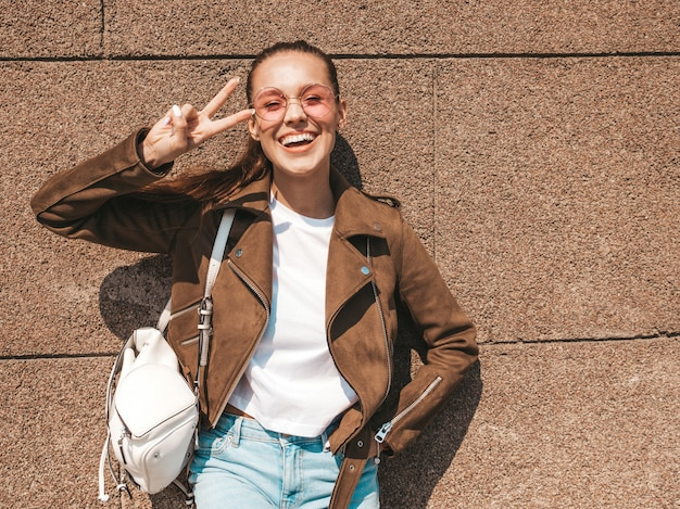 Portrait of beautiful smiling brunette model dressed in summer hipster jacket and jeans clothes